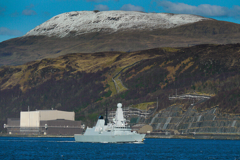 HMS Dauntless passes the Explosives Handling Jetty on Loch Long where Trident missiles are loaded into submarines